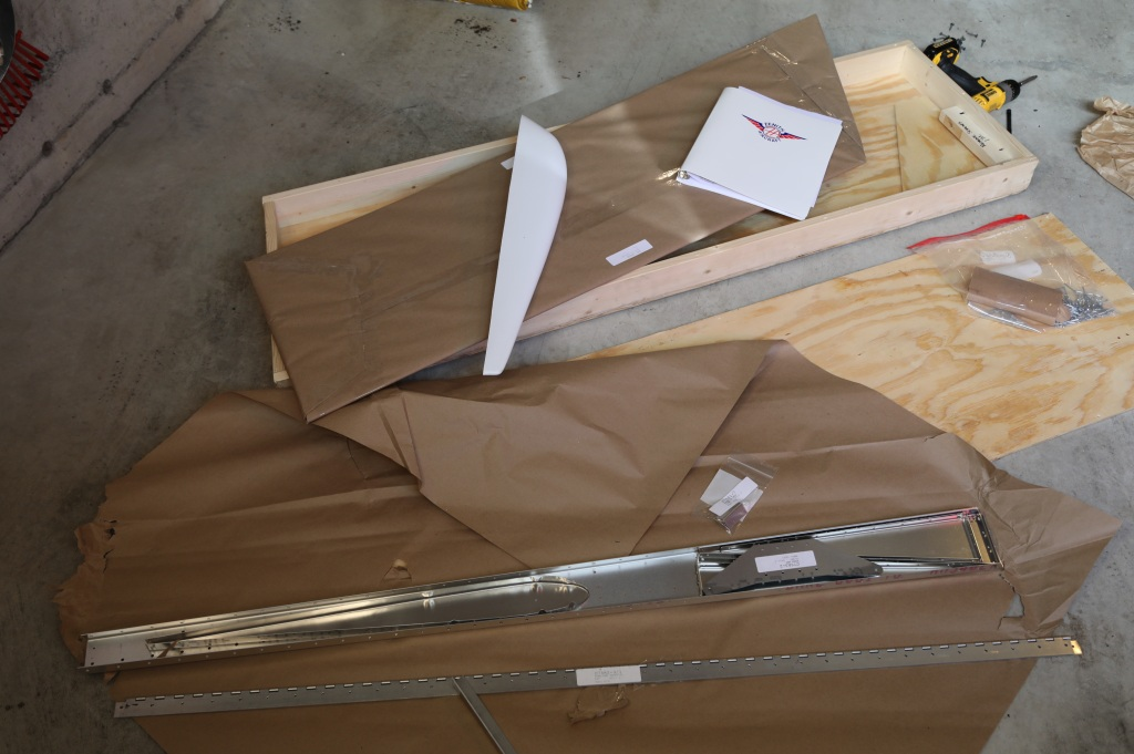 Photo of the contents of the tall, thin box, showing laid out across the packaging paper a half-dozen or so  formed, aluminum airplane parts; rivets; a plastic streamlined top cap; and a plastic-bound manual. Oh, and the electric screwdriver used to remove the box's top cover.